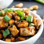 Side shot of cashew chicken in a bowl topped with green onions