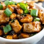 Side shot of cashew chicken in a bowl topped with green onions and recipe title on bottom of photo