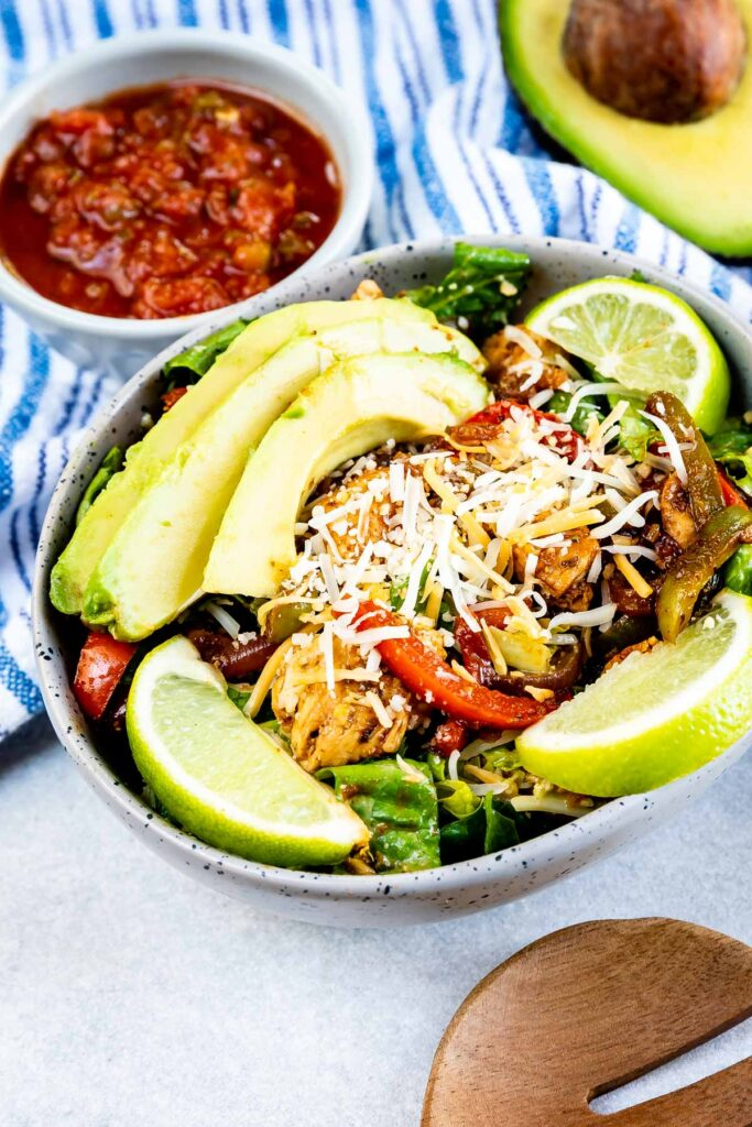 Fajita salad in a salad bowl with extra salad and an avocado next to it