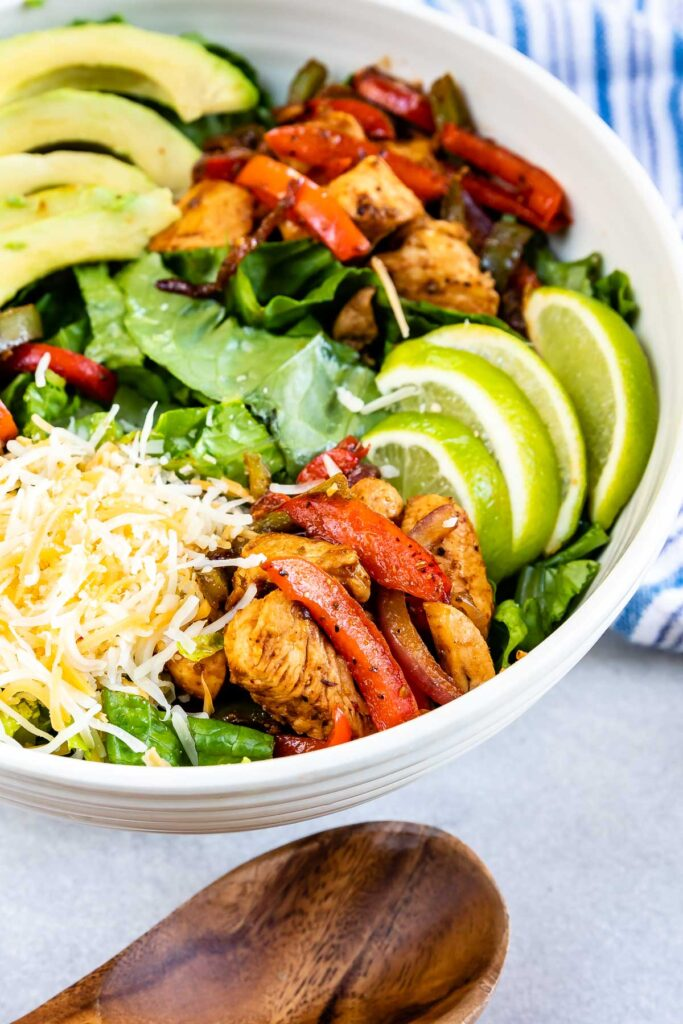 Overhead close up shot of fajita salad in serving bowl before being tossed together and dressed
