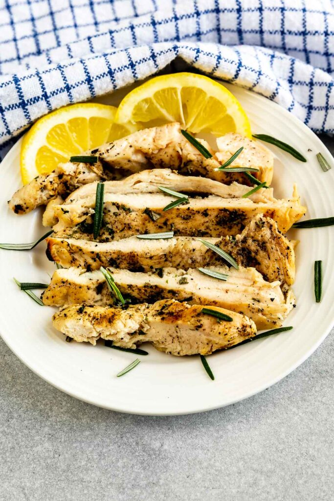Overhead shot of a plate full of grilled chicken with lemon and herbs