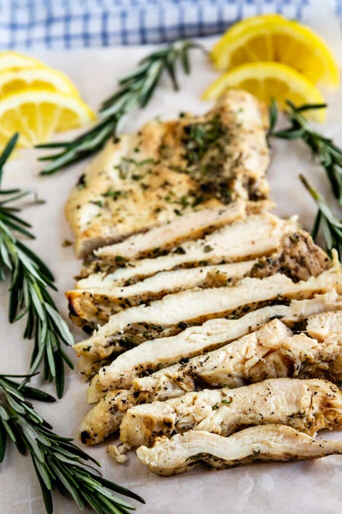 Grilled chicken sliced on a cutting board surrounded by lemon slices and herbs