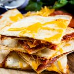Stack of four pieces of pepperoni pizza quesadillas on a cutting board