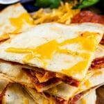 Stack of four pieces of pepperoni pizza quesadillas on a cutting board with recipe title on top of image