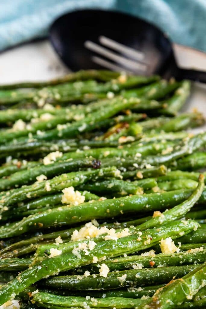 Close up shot of roasted green beans on a serving plate with serving spoon