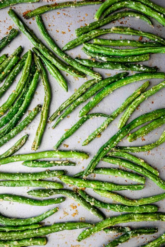 Overhead shot of roasted green beans on a sheet pan