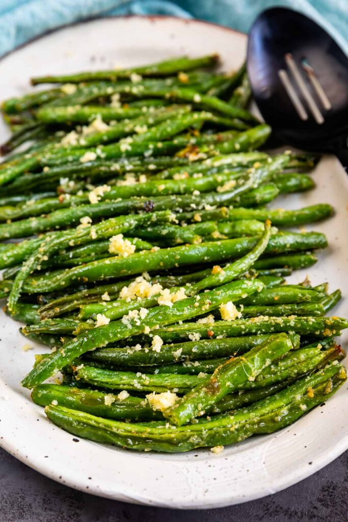 Roasted green beans on a serving plate with serving spoon