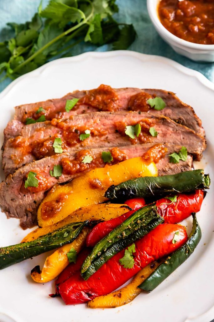 Steak and peppers on a plate with sauce behind it