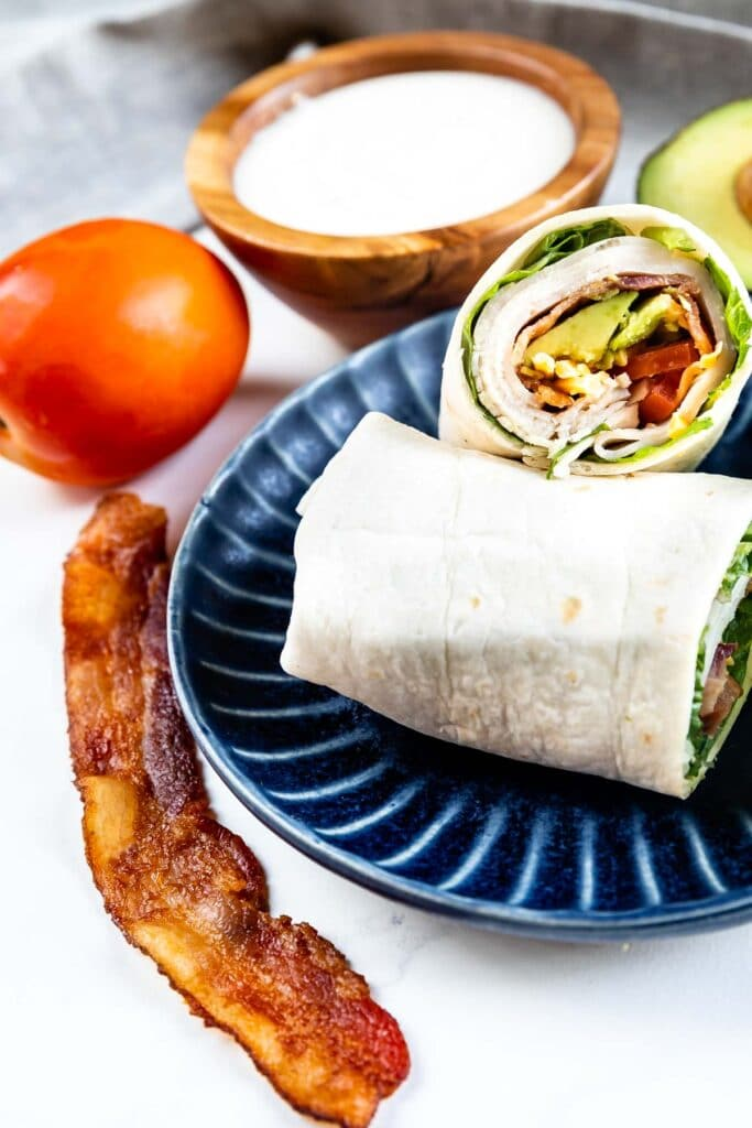 Turkey bacon wrap cut in half on a blue plate with ingredients around it