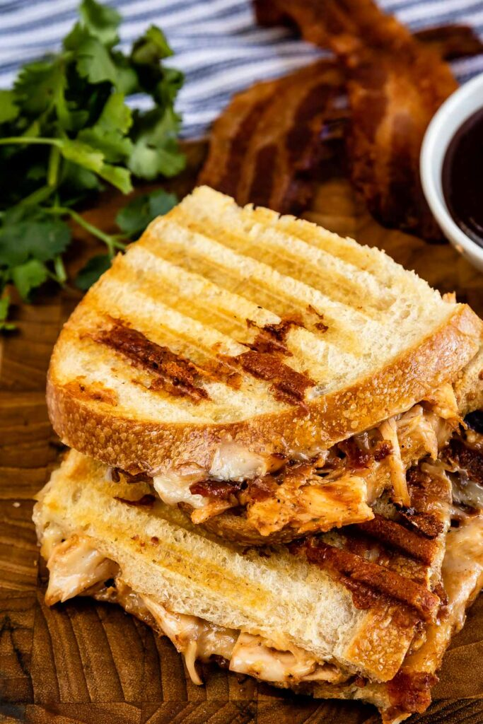 Overhead shot of bbq chicken panini cut in half on a wooden cutting board