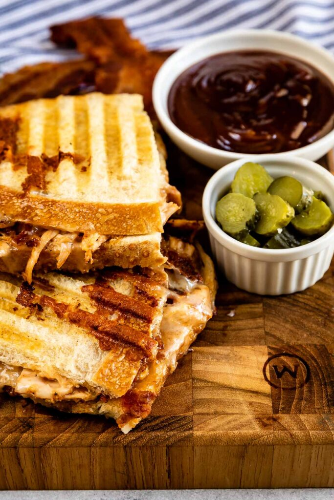BBQ Chicken Panini on a cutting board with pickles and bbq sauce