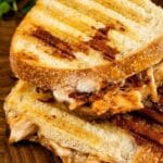 Overhead shot of bbq chicken panini cut in half on a wooden cutting board with recipe title on bottom of photo