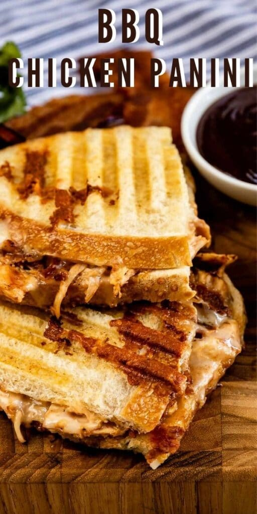 Overhead shot of bbq chicken panini cut in half on a wooden cutting board with recipe title on top of photo