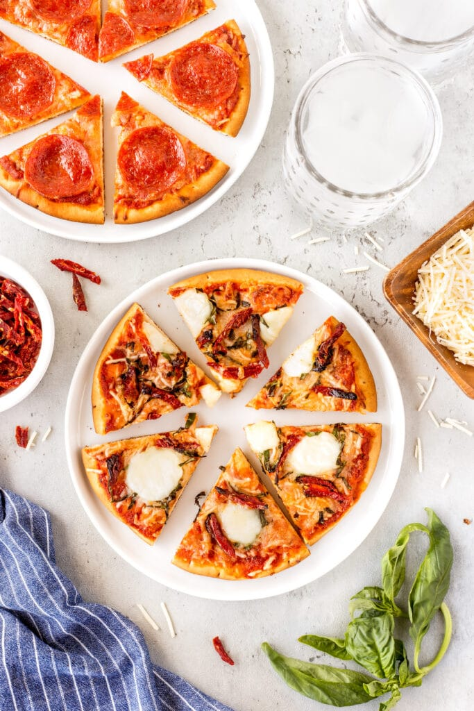 Overhead view of two easy pita pizzas cut into slices on plates