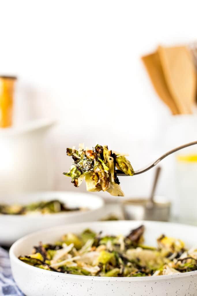 Big bite of grilled caesar salad on a fork