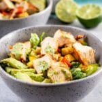 Two low carb grilled chicken power bowls with salsa and limes in background