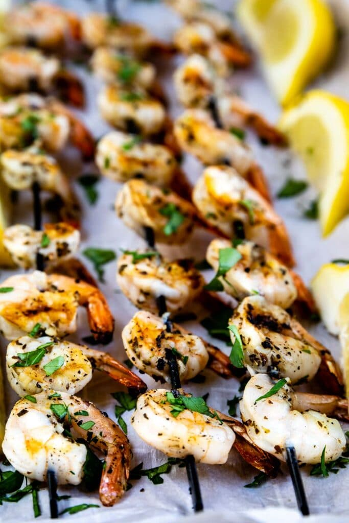 Three skewers of shrimp kabobs surrounded by lemons