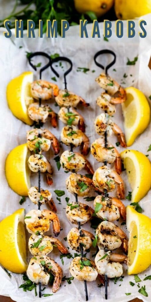 Overhead view of three skewers of shrimp kabobs surrounded by lemons with recipe title on top of image
