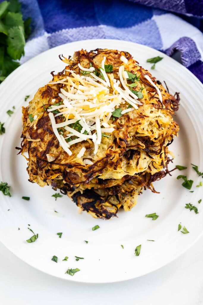 Overhead shot of spaghetti squash hash browns with cheese on top on a white plate