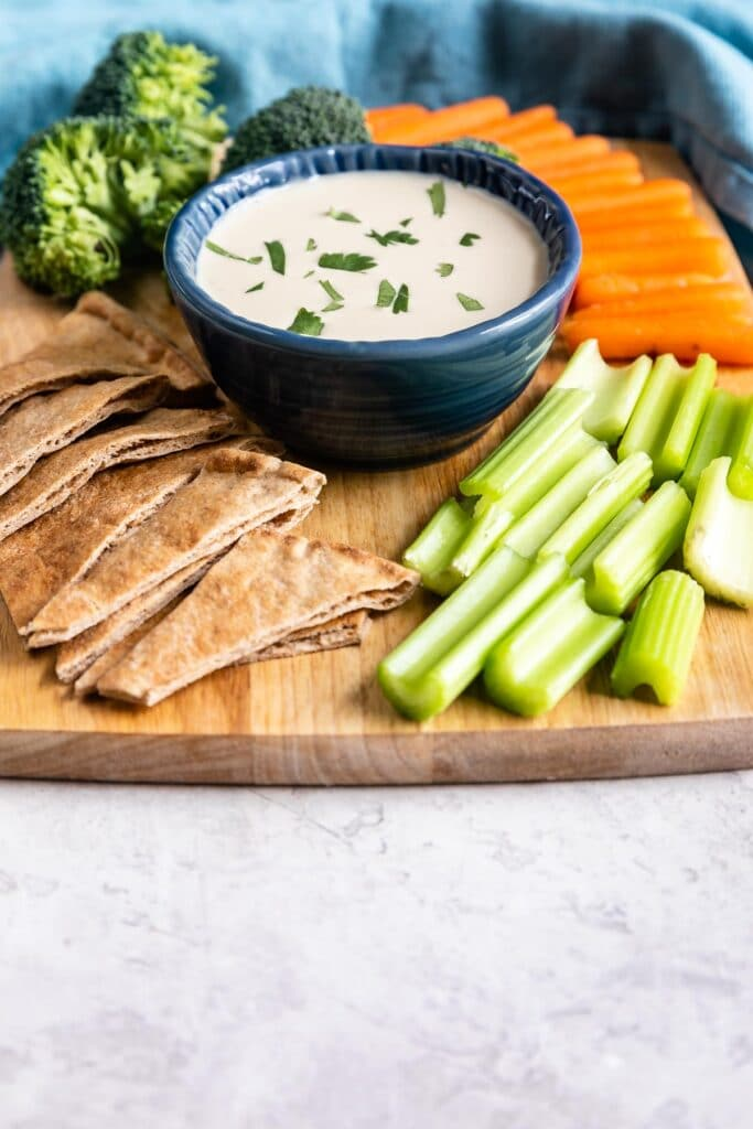 Wooden cutting board filled with veggies and tahini sauce in the middle as a dip