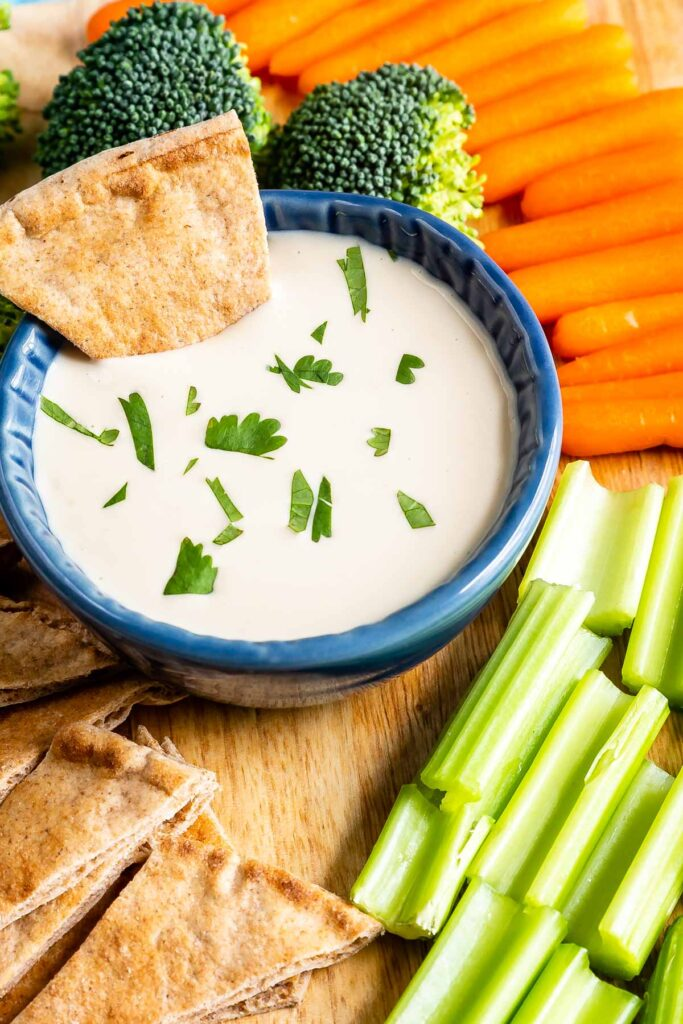 Overhead shot of tahini sauce in a dipping cup with a pita bread dipped in