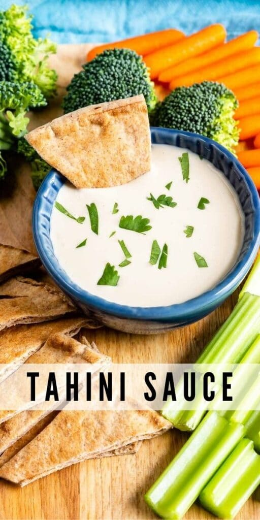 Overhead shot of tahini sauce in a dipping cup with a pita bread dipped in and recipe title on bottom of photo