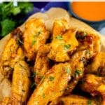 Overhead view of crispy air fryer chicken wings with buffalo sauce behind it with recipe title on top of photo
