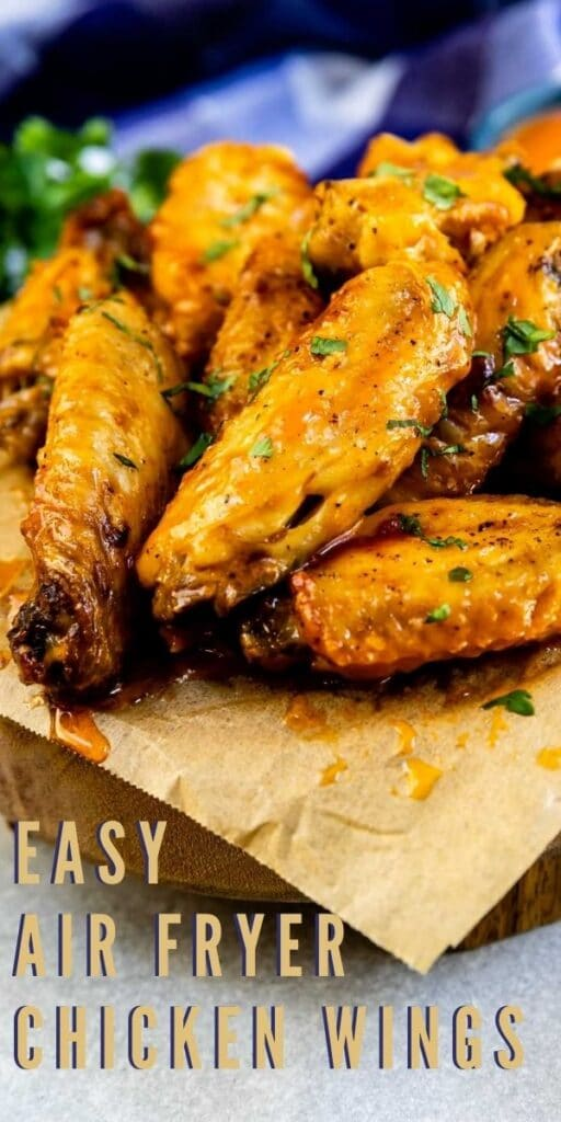 Crispy air fryer chicken wings on a wooden plate with recipe title on bottom of photo