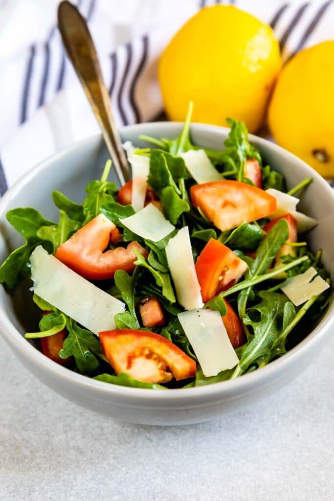 Bowl full of arugula salad with lemons in background