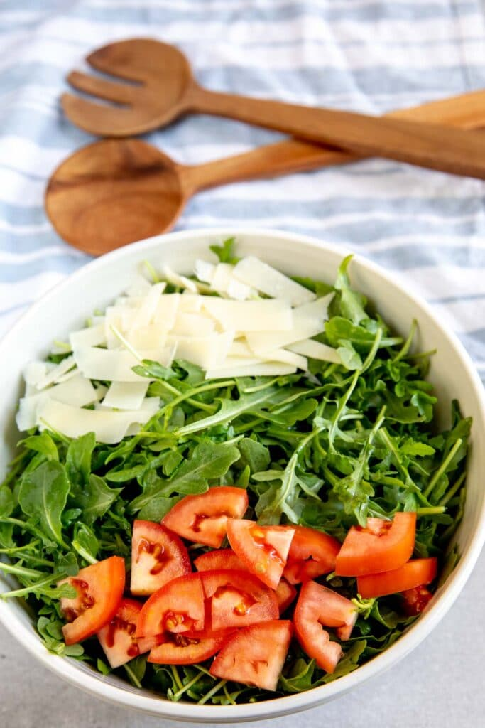Overhead shot of arugula salad ingredients in salad bowl before being mixed together
