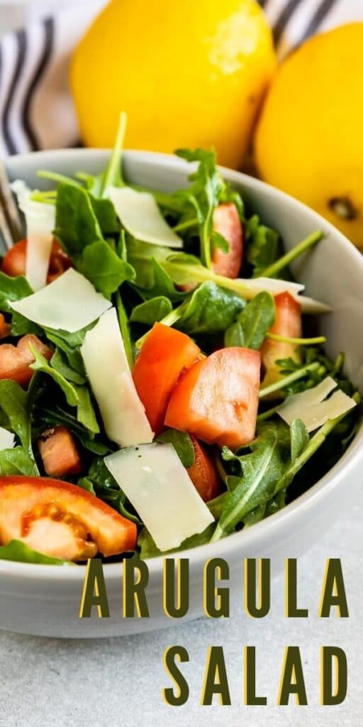 Bowl full of arugula salad with lemons in background with recipe title on bottom of photo