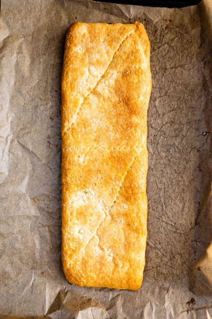 Overhead shot of baked garlic breadsticks on a sheet pan before being cut