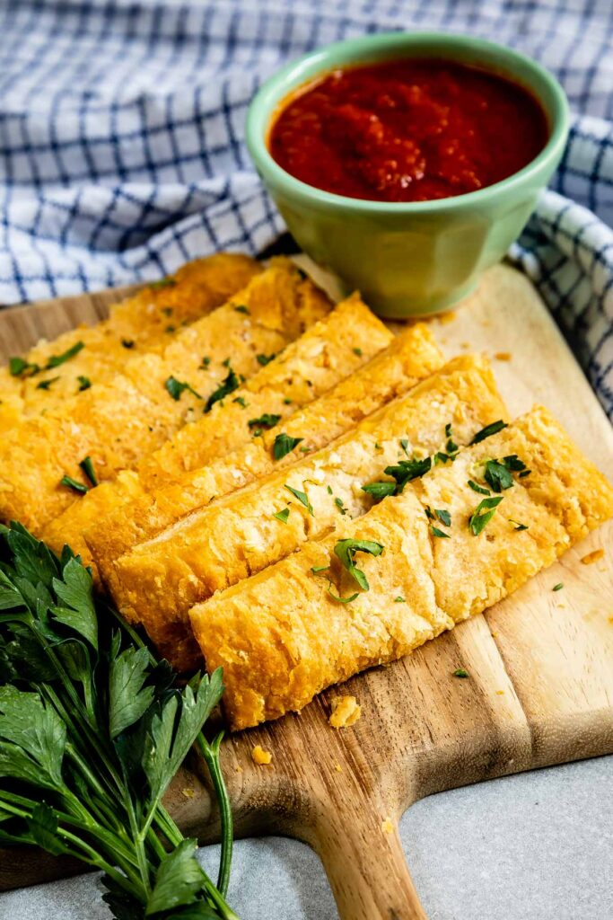 Cheesy Garlic Breadsticks on a cutting board with marinara sauce