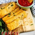 Cheesy Garlic Breadsticks on a cutting board with marinara sauce and recipe title on bottom of photo