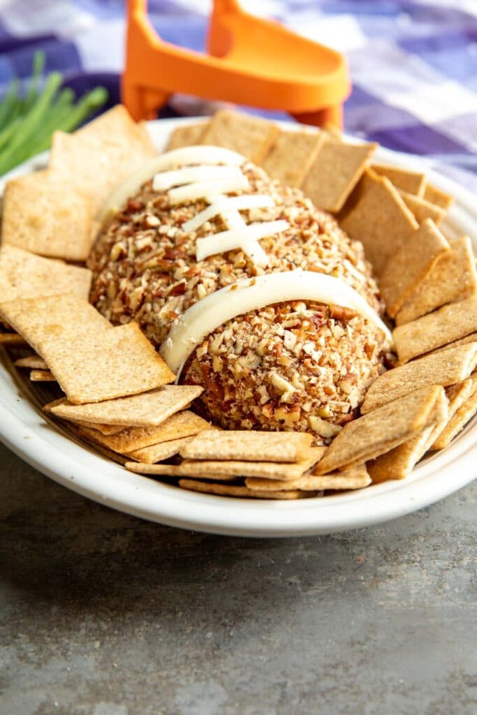 Football Cheese Ball on a serving plate surrounded by crackers