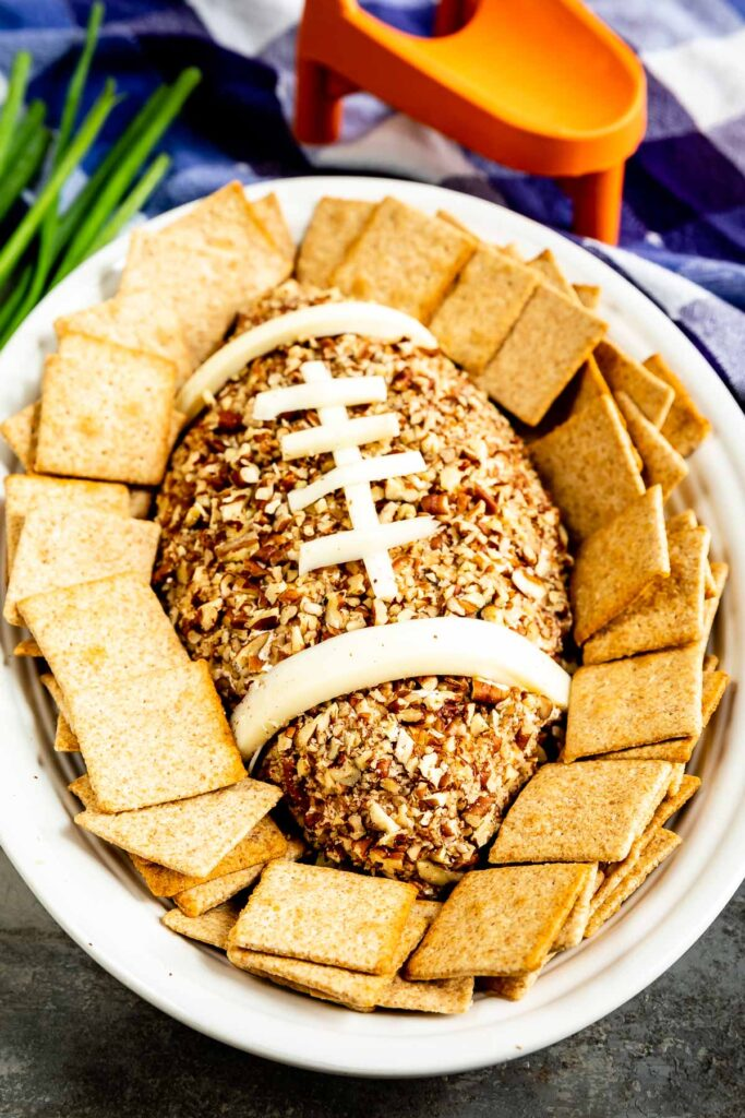 Overhead shot of Football Cheese Ball on a serving plate surrounded by crackers