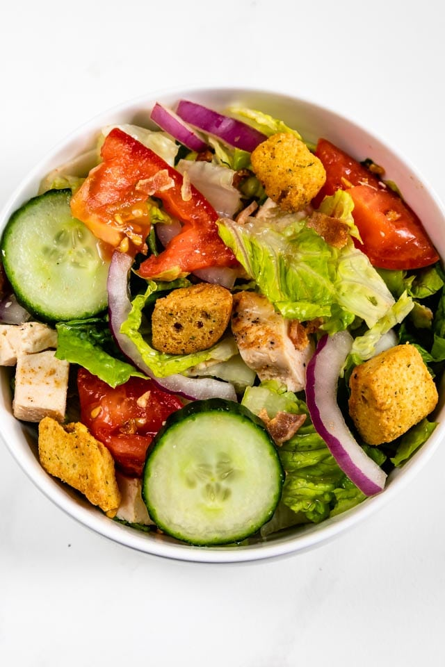 Overhead shot of simple house salad with croutons on top
