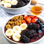 Two acai bowls with honey in between them