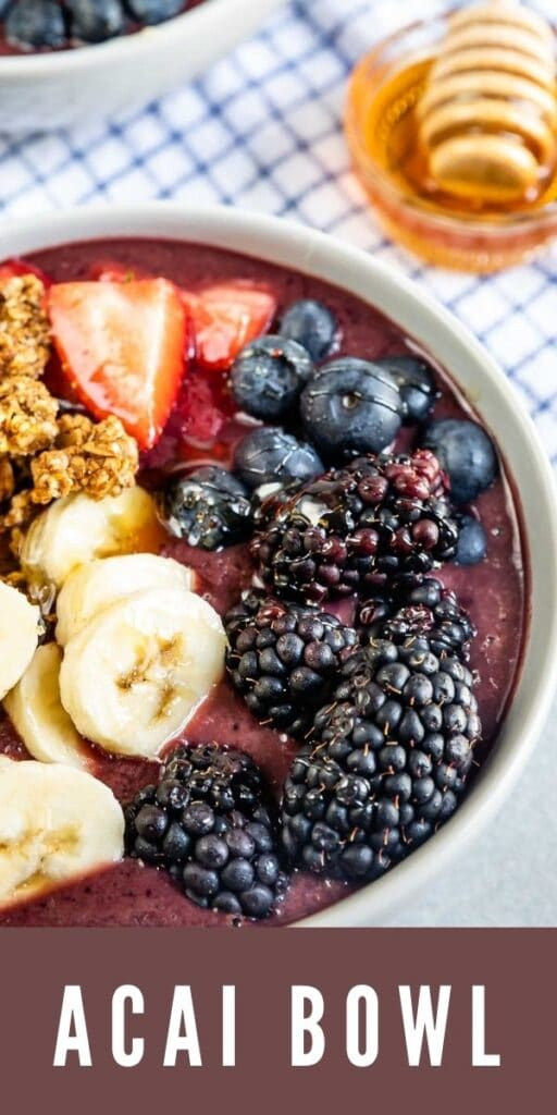 Close up overhead shot of acai bowl with honey in background and recipe title on bottom of photo